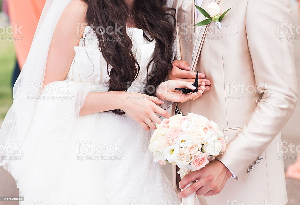 bride is holding a butterfly in his hands stock photo