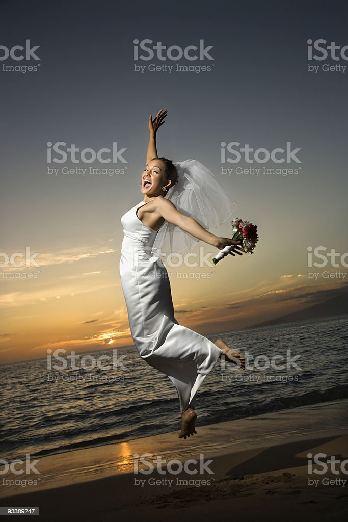 Bride jumping on beach. royalty-free stock photo