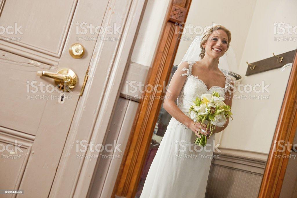 Bride looking at herself in mirror wedding dress veil bouquet stock photo