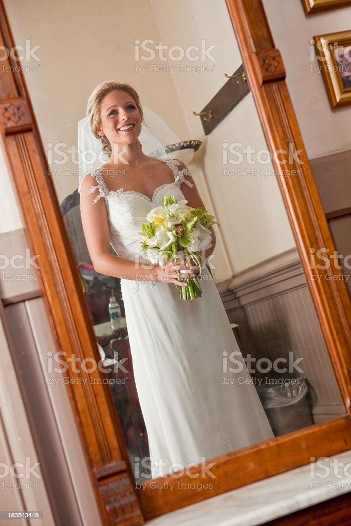 Bride looking in mirror wearing wedding dress veil holding bouquet stock photo