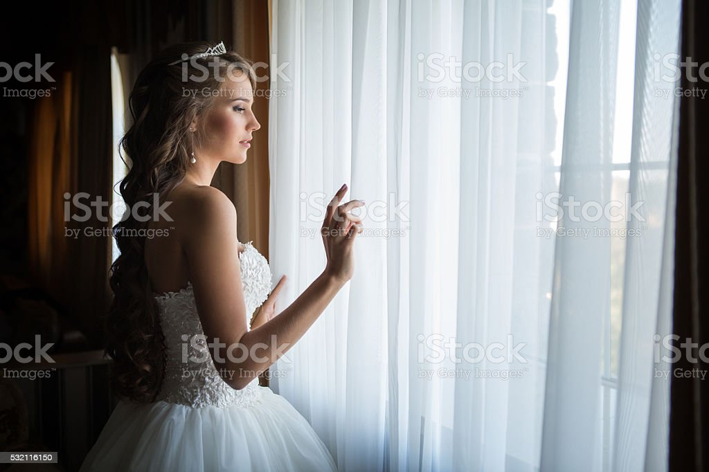 Bride looks out of the window,wedding day stock photo
