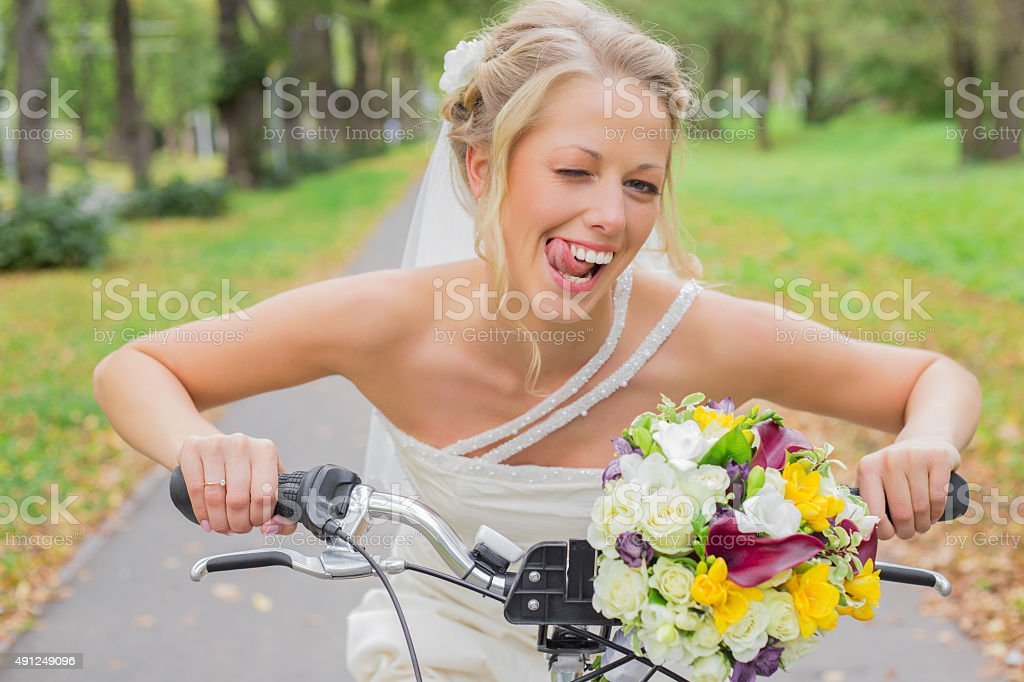 Bride on a bicycle being flirty stock photo