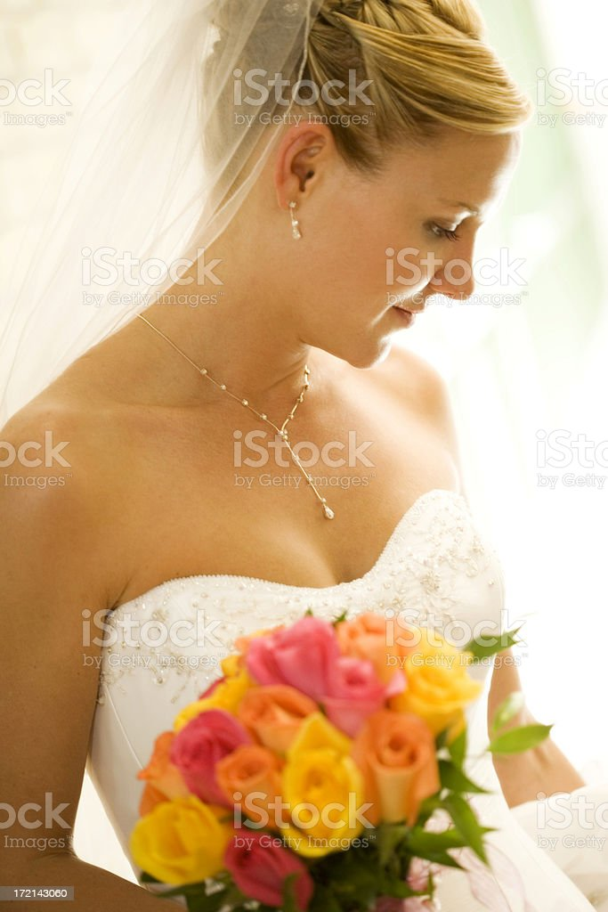 A bride on her wedding day holding flowers stock photo