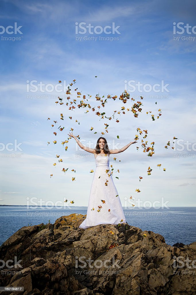 Bride on oceanfront throwing flowers in air stock photo