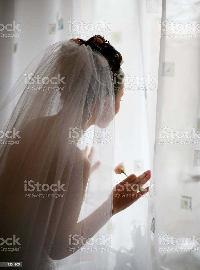 Bride peering out the window with a flower in her hand royalty-free stock photo