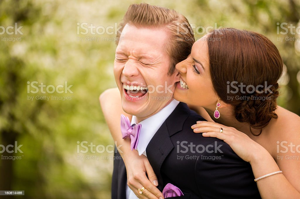 Bride playfully biting groom in his earlobe stock photo