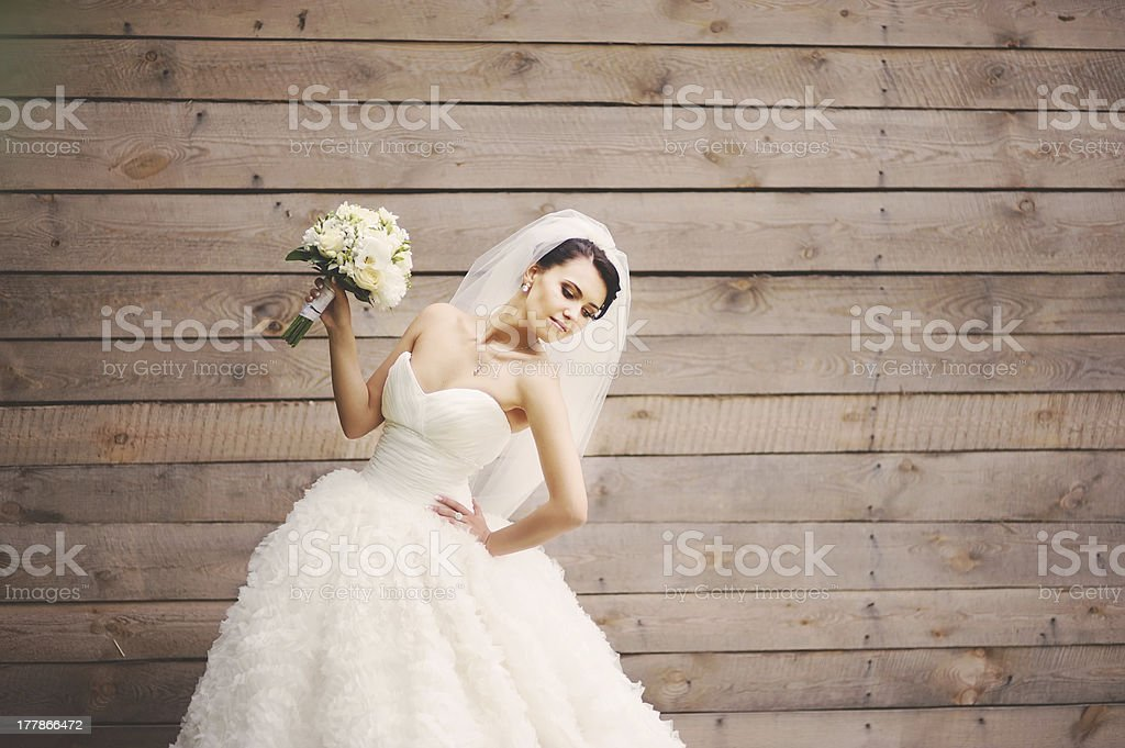 Bride posing with bouquet of white flowers against wood stock photo