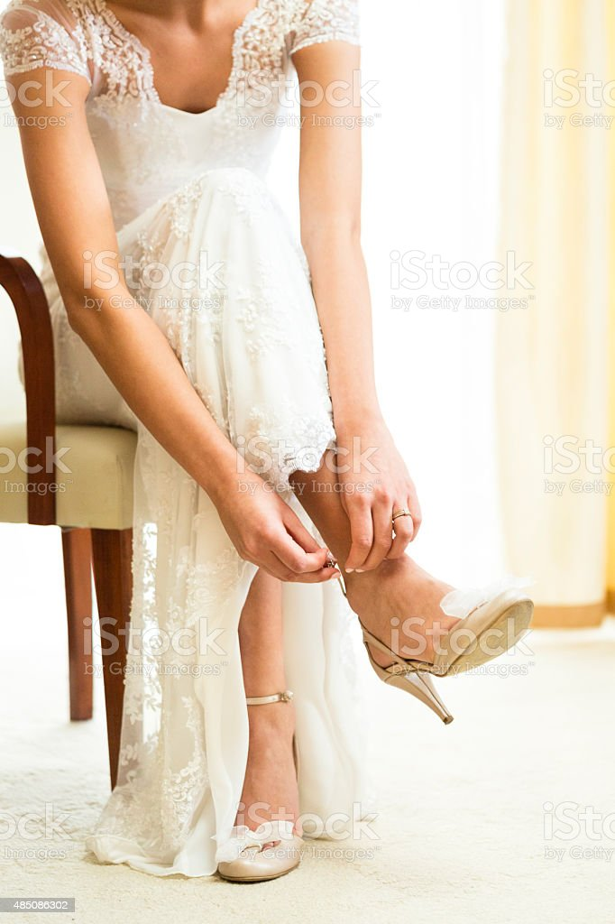 Bride preparation, putting wedding shoes on stock photo