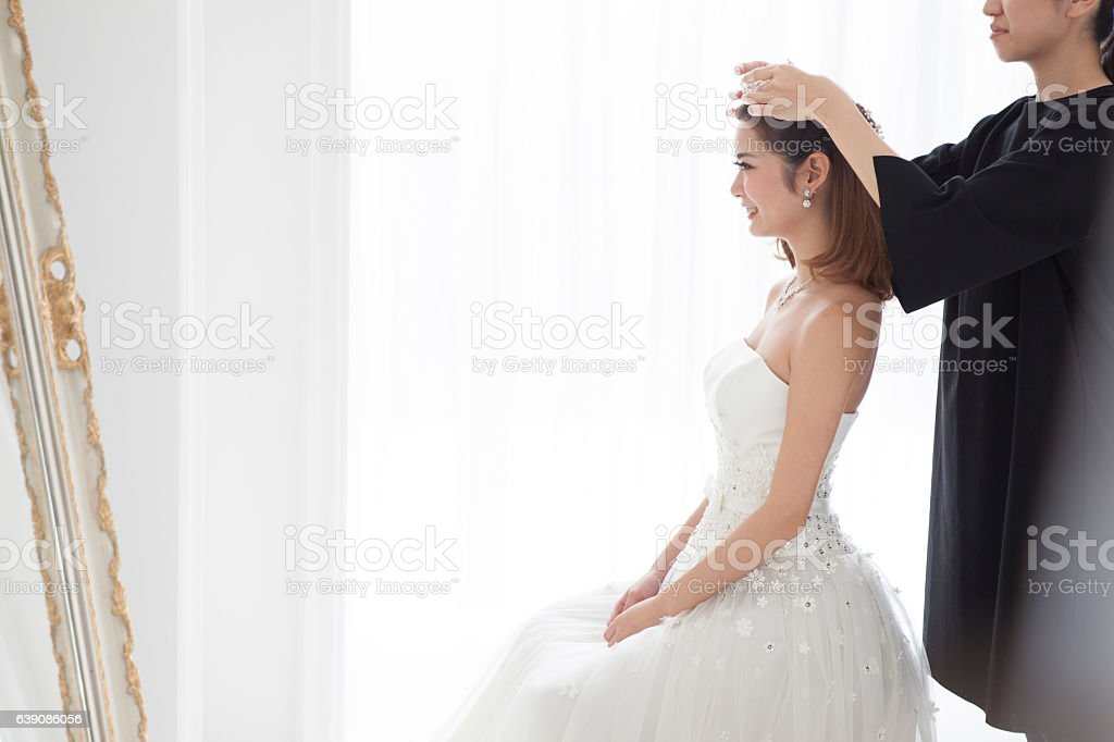 Bride puts a crown on her head. stock photo