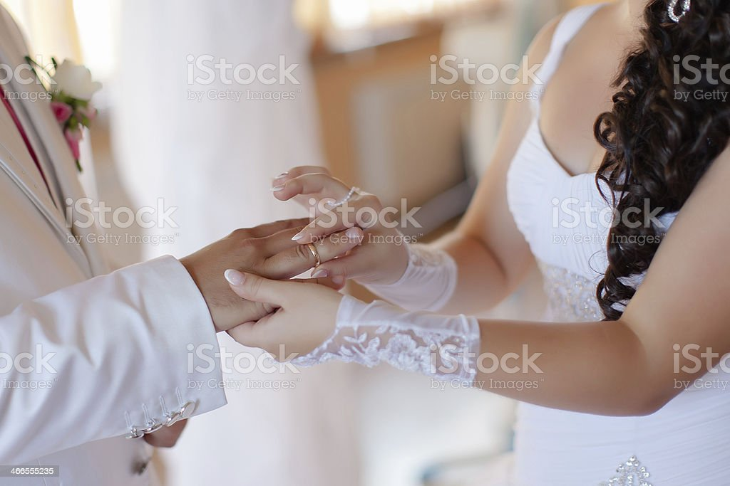 Bride puts on a wedding ring to a groom stock photo