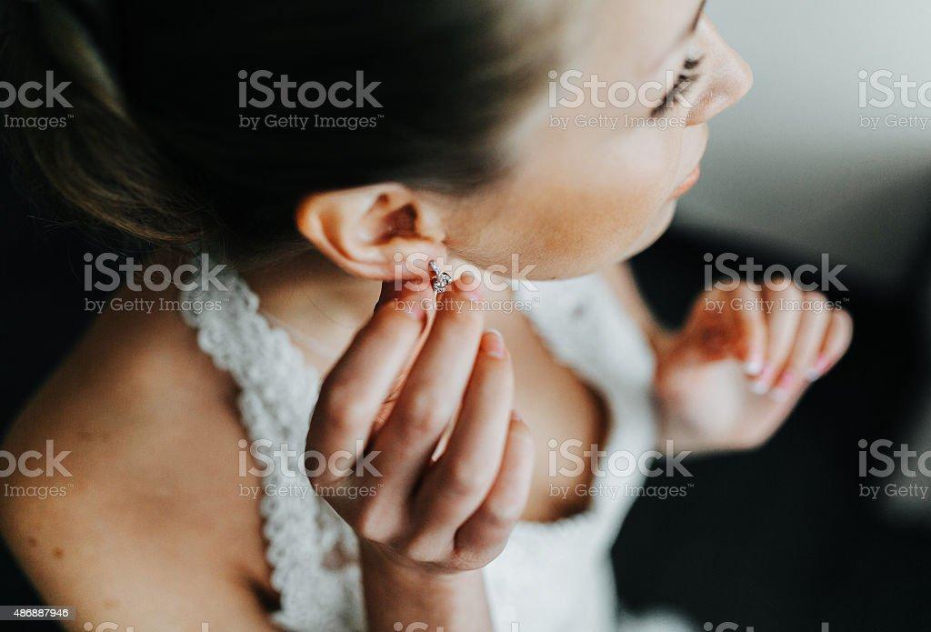 Bride puts on earrings stock photo
