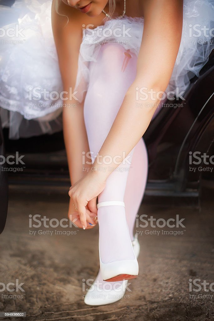bride puts on shoes while sitting in the car stock photo