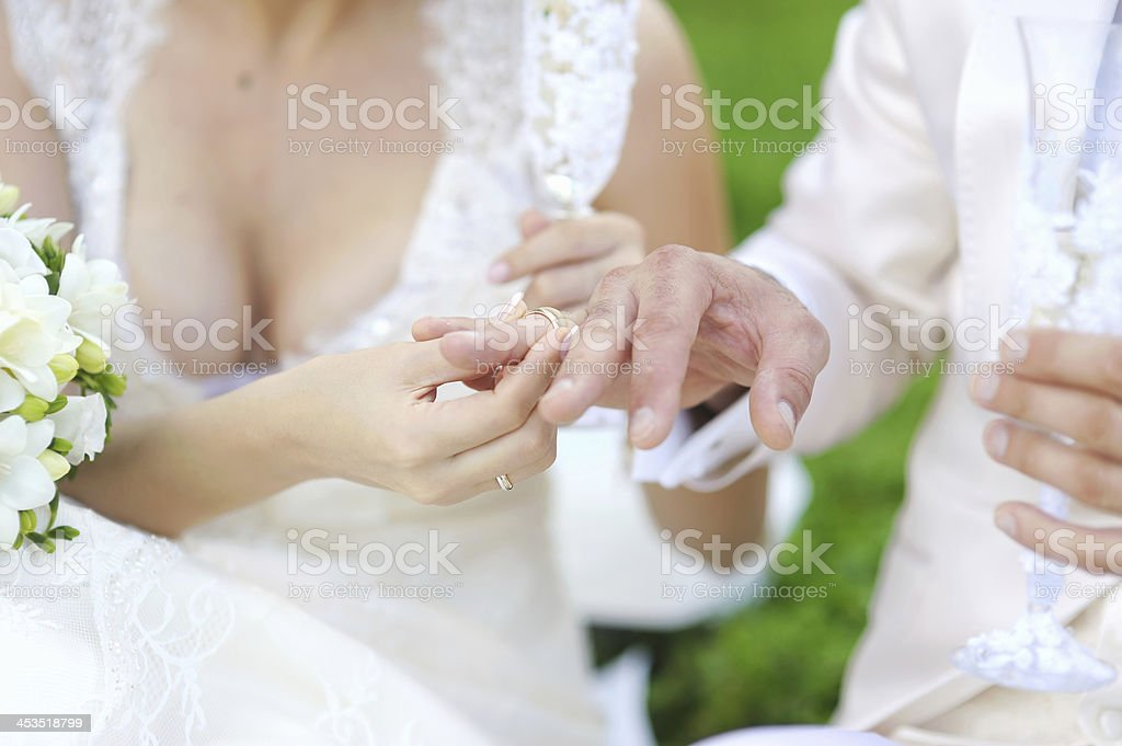 Bride putting a ring on groom's finger royalty-free stock photo