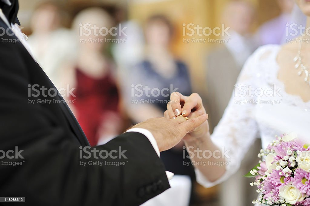 Bride putting a wedding ring on groom's finger royalty-free stock photo