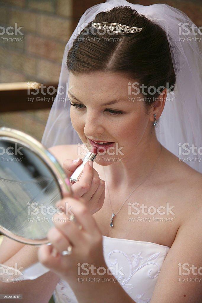 Bride putting lipstcik stock photo