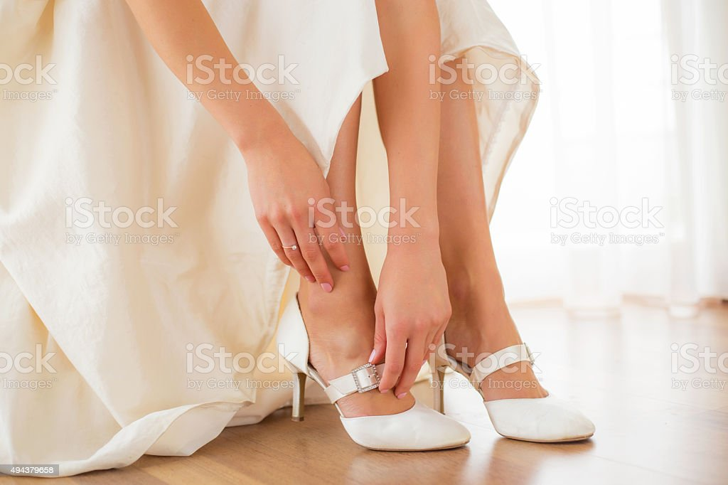 Bride putting on her white shoes stock photo