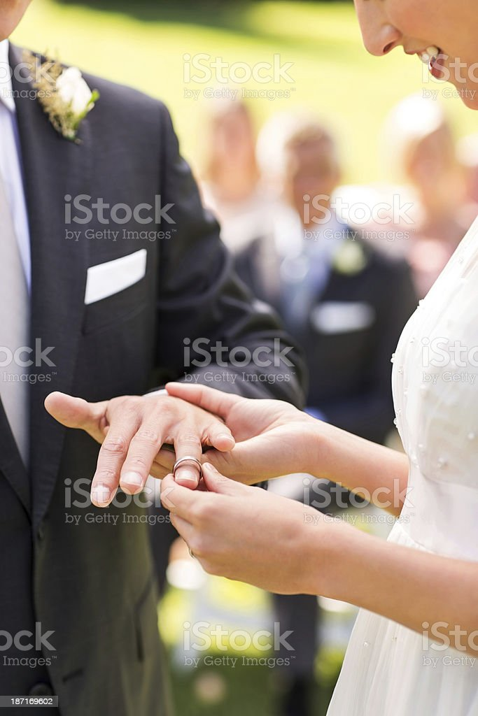 Bride Putting Ring On Groom's Finger During Wedding Ceremony stock photo