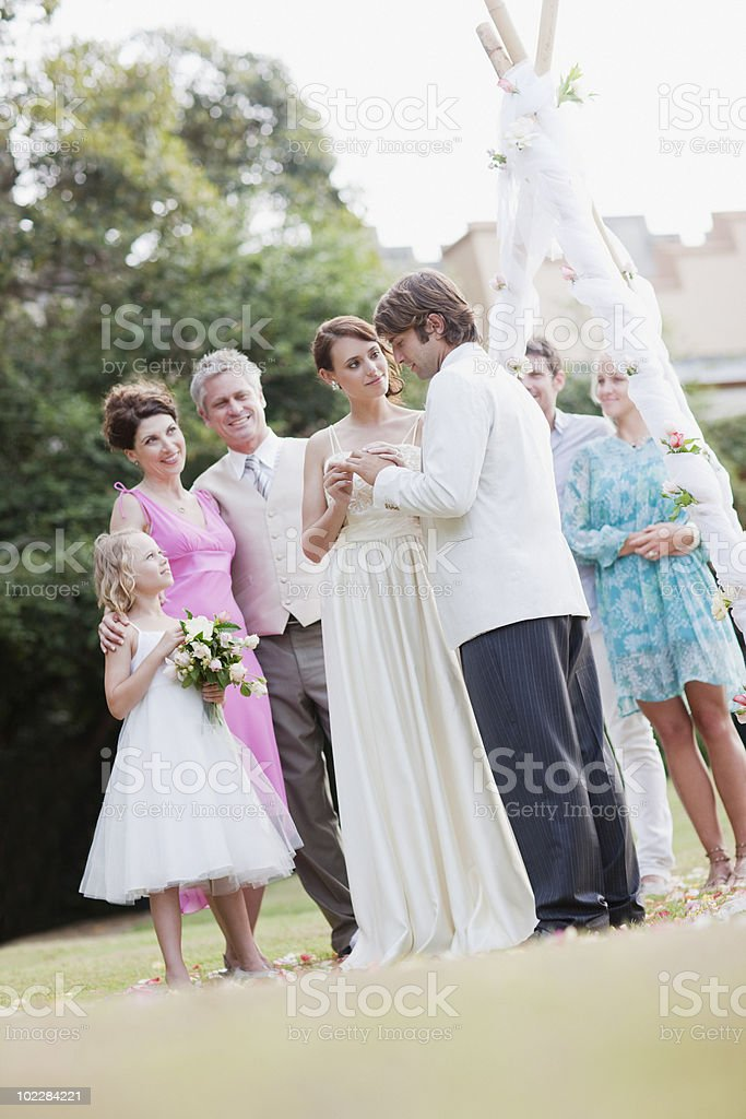 Bride putting ring on grooms finger royalty-free stock photo