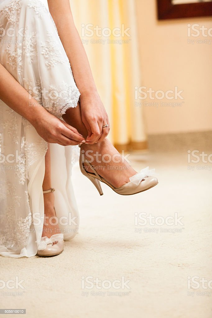 Bride putting shoes on stock photo