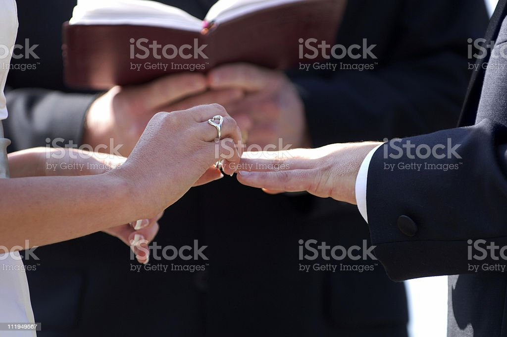 Bride putting Wedding Band on Groom Close Up stock photo