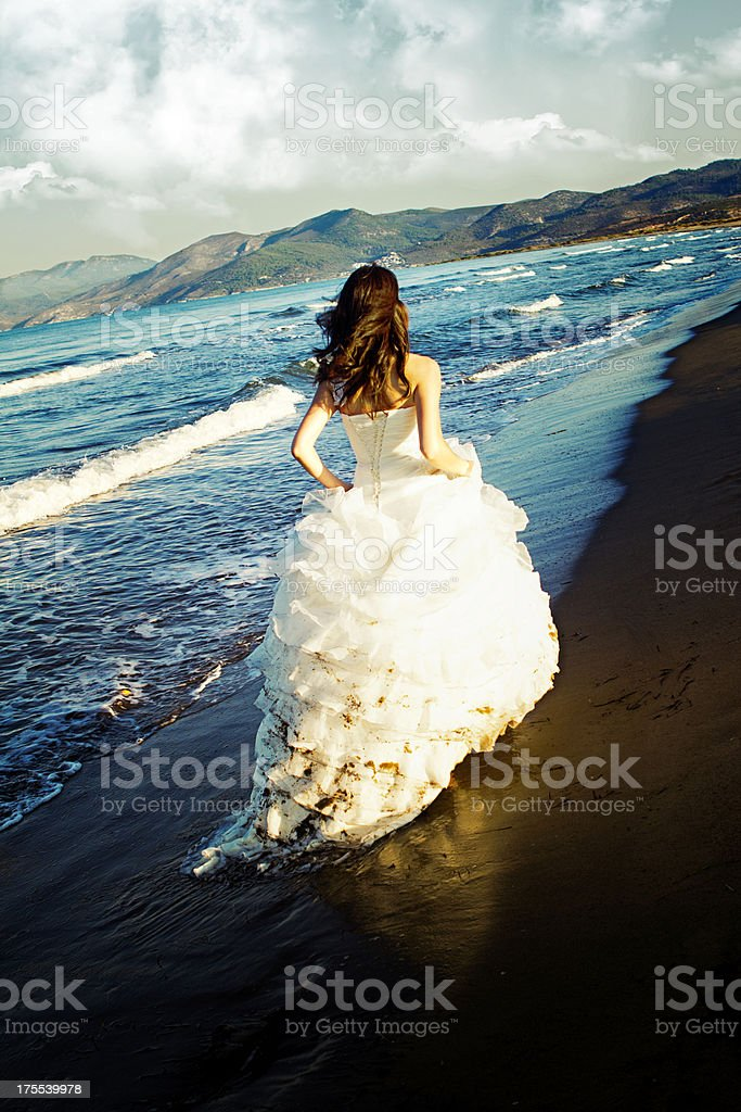 A bride, running at the surf's edge, in her wedding dress stock photo