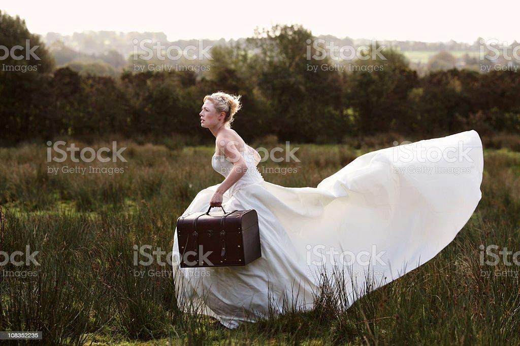 Bride running away stock photo