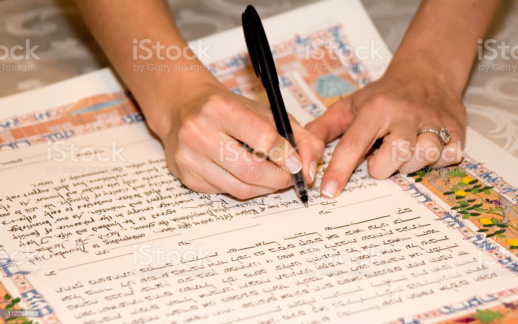 bride signing a jewish katuba marraige certificate stock photo