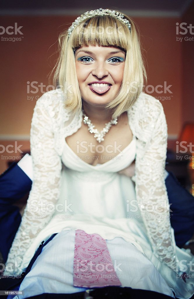 Bride sits on the groom. They have fun and play royalty-free stock photo