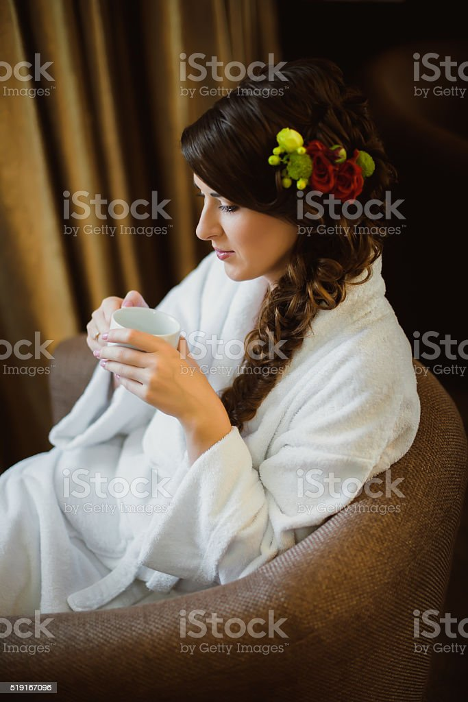 Bride sitting in a chair drinking coffee stock photo