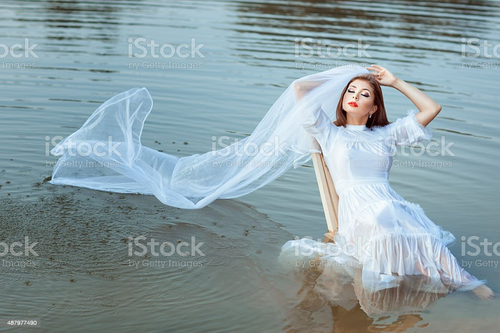Bride sitting in a lake, her veil wet. stock photo