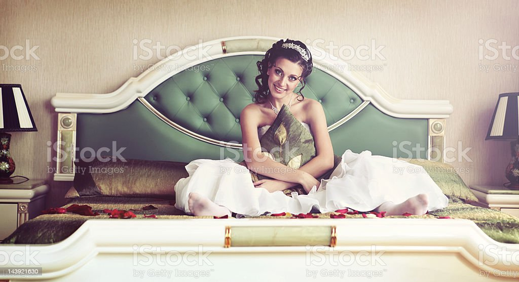 Bride Sitting on a Bed in the Bedroom. royalty-free stock photo