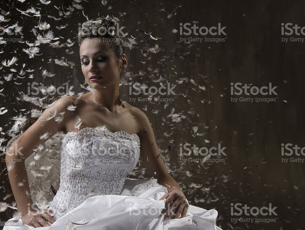 Bride Sitting on Chair with Feathers Floating Around Her royalty-free stock photo