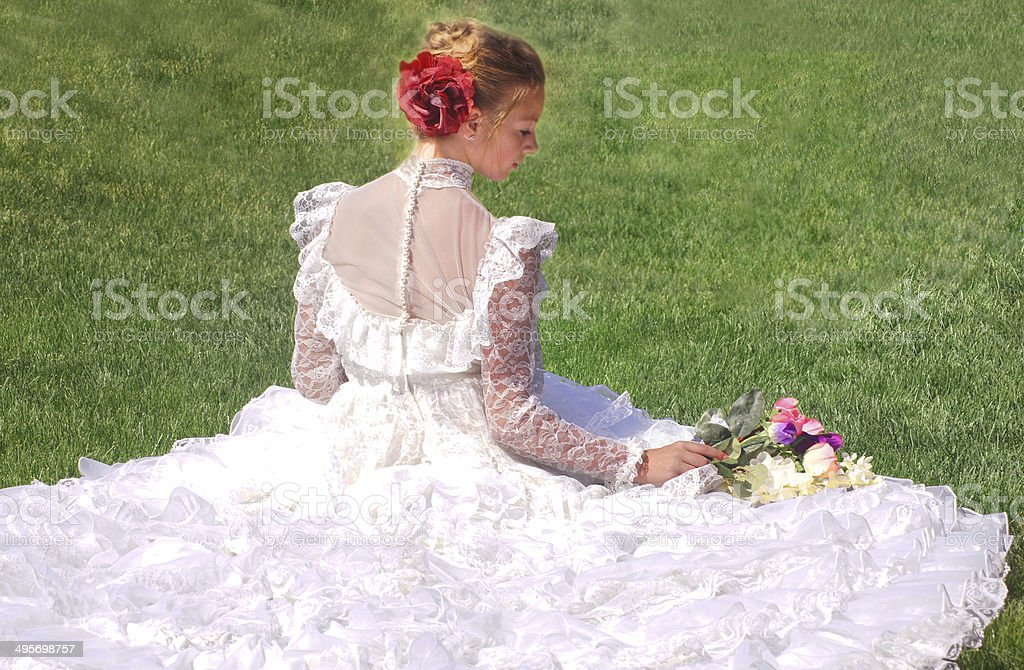 Bride Sitting On Lawn, Profile, Looking at Bouquet stock photo