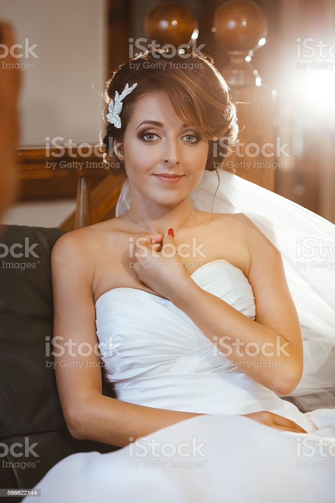 Bride sitting on sofa and smiling stock photo