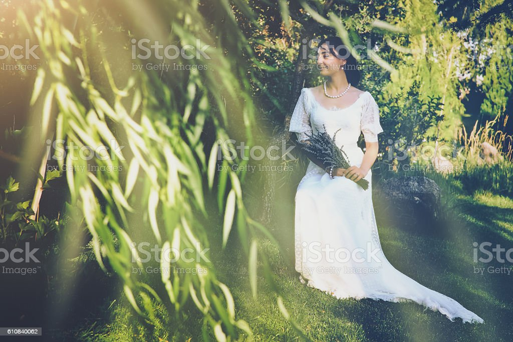 Bride sitting with purple lavender bouquet stock photo