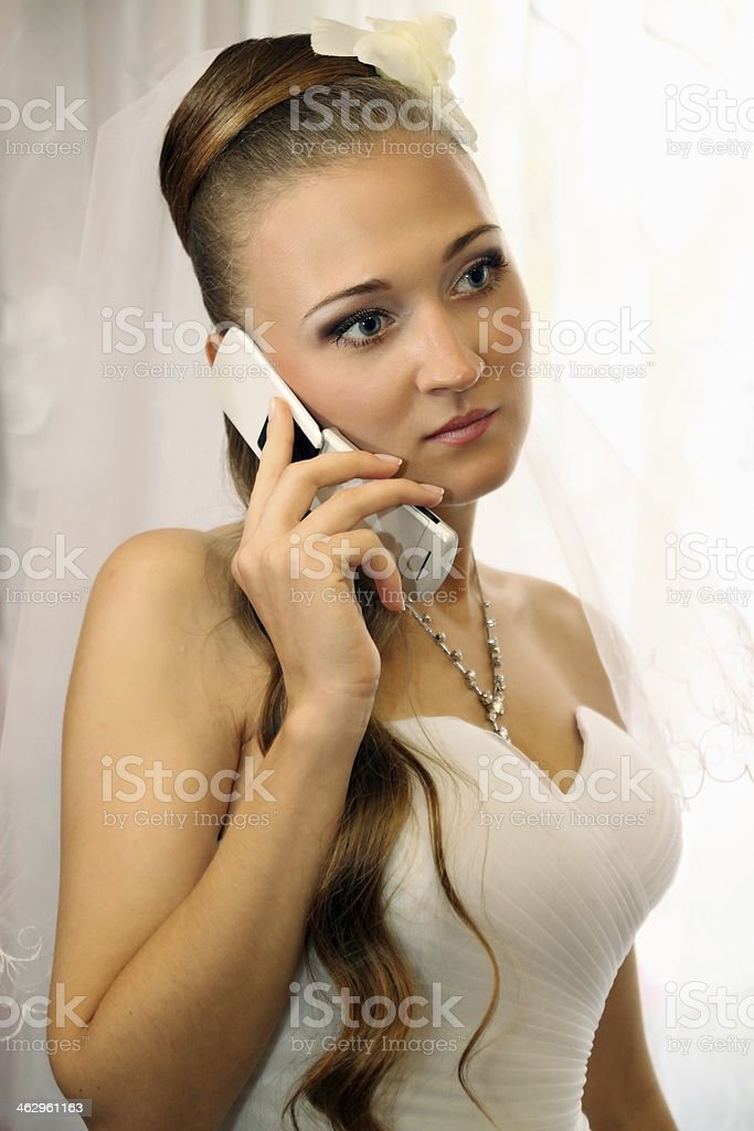 bride speaks on the phone stock photo