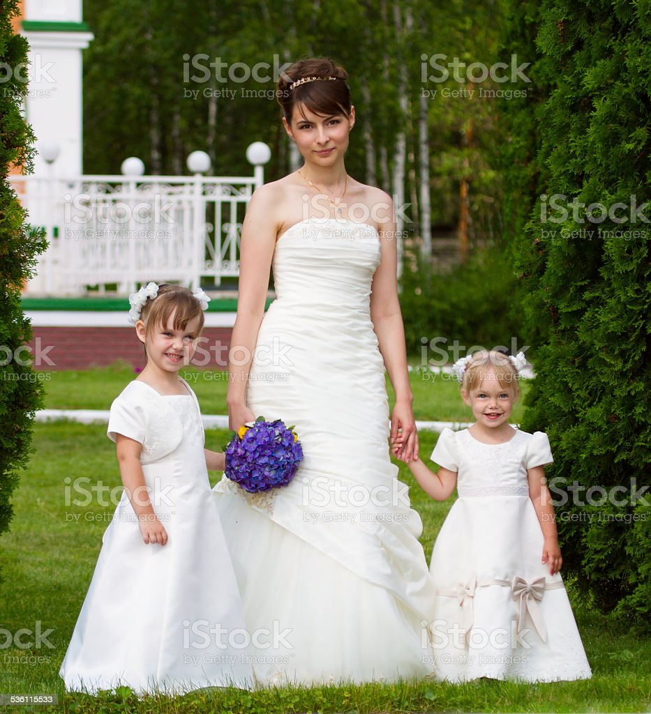 Bride stand with little girls stock photo