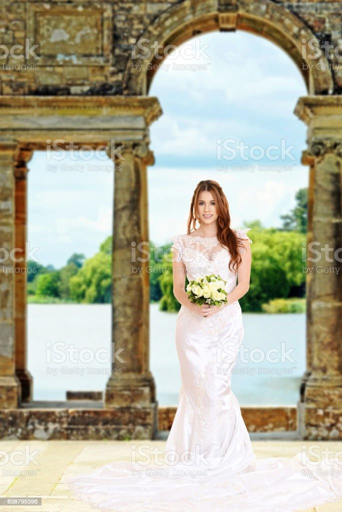 bride standing by stone arch and lake stock photo