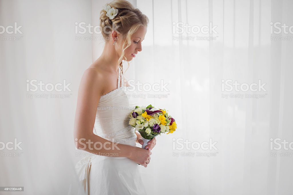 Bride standing by the window with flowers in her hand stock photo