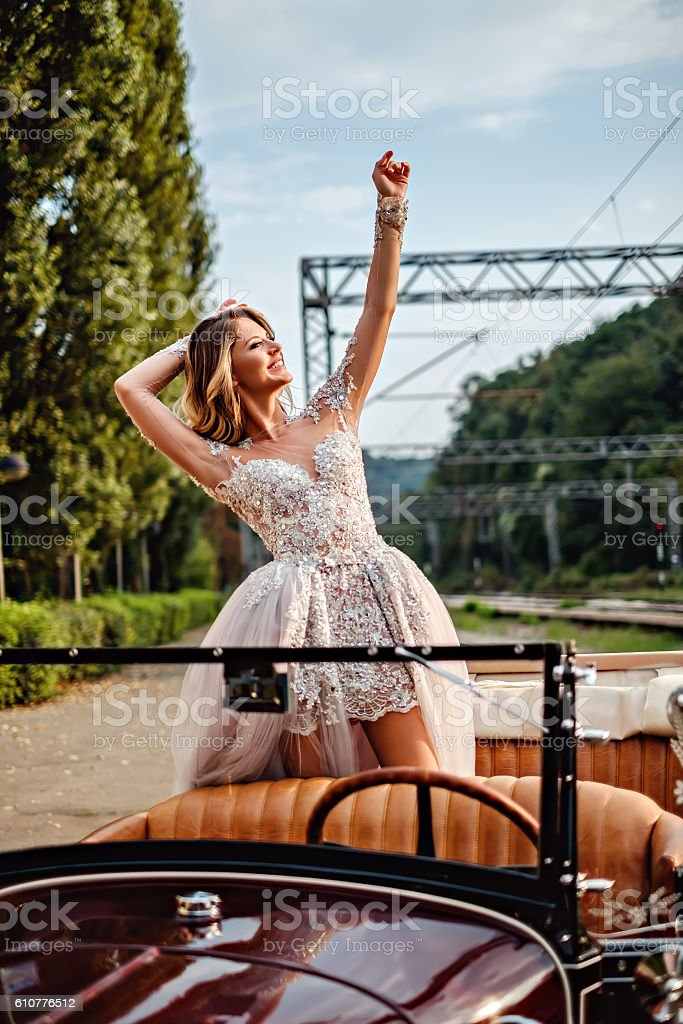 Bride standing in classic convertible lifting hands up stock photo