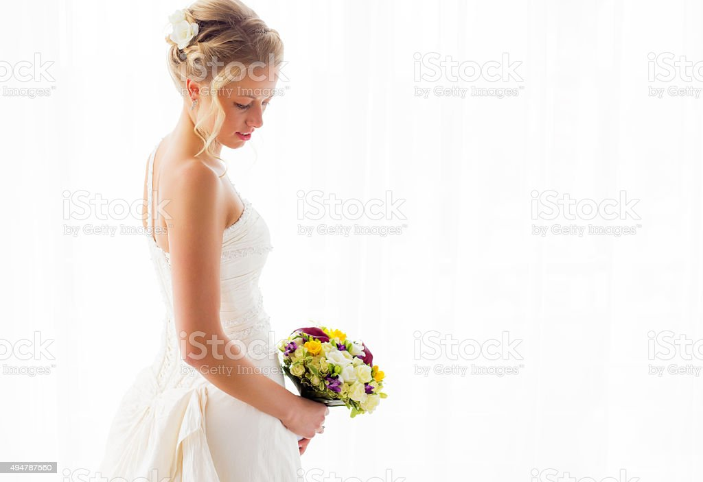 Bride standing in her wedding dress and bouquet stock photo