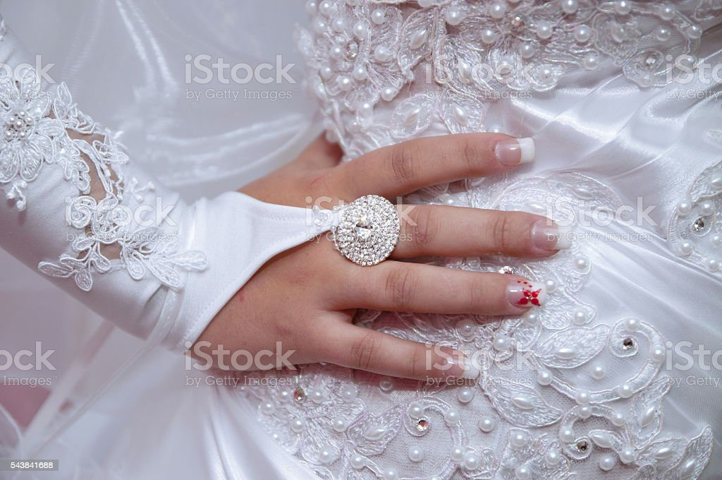 Bride standing with hand on hip in her wedding dress stock photo