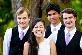 Bride standing with her three groomsmen under large tree