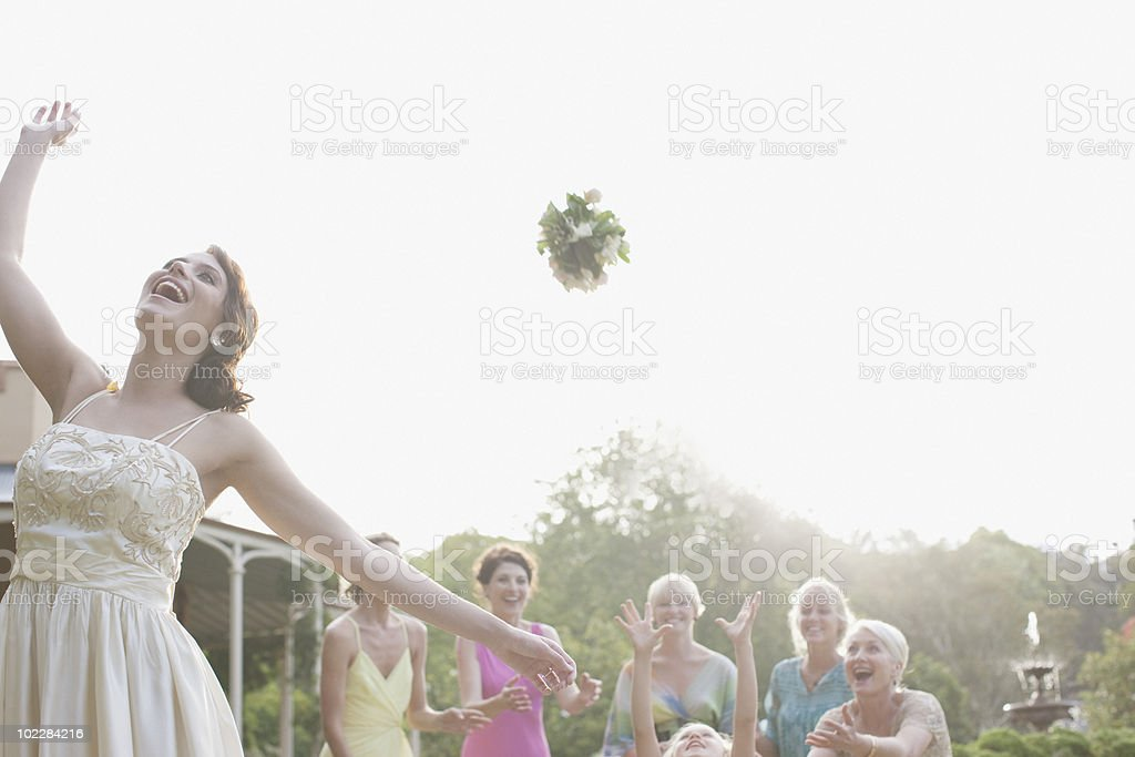 Bride throwing bouquet at wedding reception stock photo
