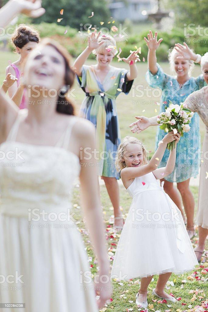 Bride throwing bouquet at wedding reception stock photo