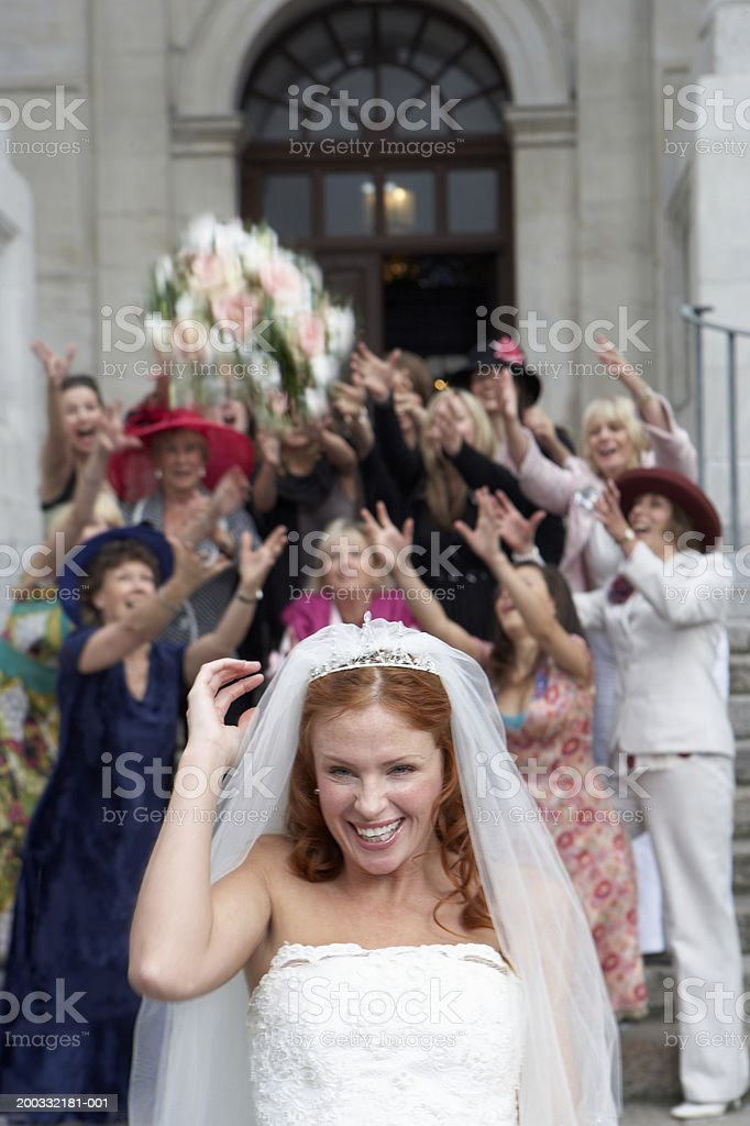 Bride throwing bouquet over head to crowd standing on steps to church stock photo