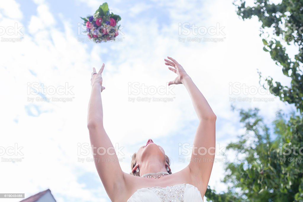Bride throwing flower bouquet at wedding stock photo