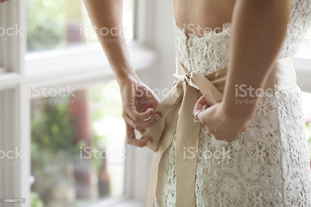 Bride Tying Wedding Dress stock photo