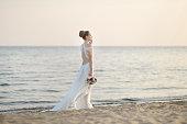 Bride walking along sea coast on sunset