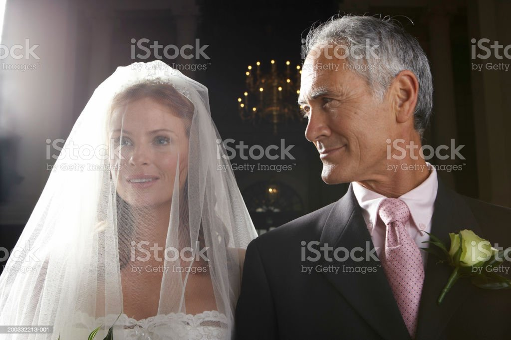 Bride walking down aisle, arm linked with father's, smiling, close-up stock photo